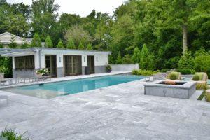 Terrassenplatten aus Stein mit Grill und Poolrand aus Steinplatten in grau