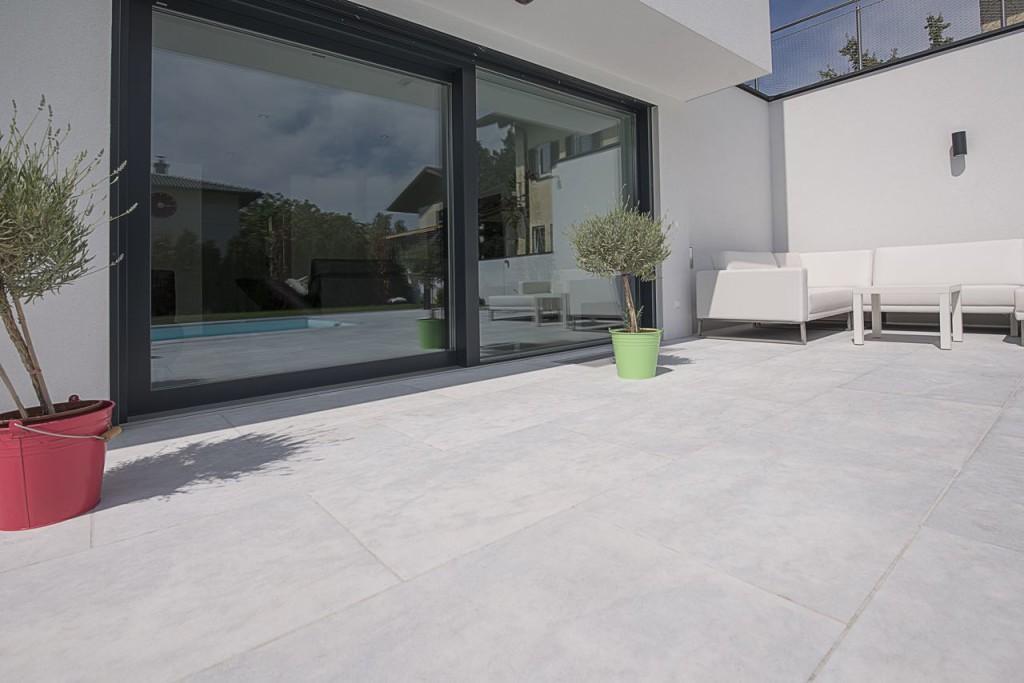 Terrassenplatten aus Kristallmarmorin grau vor modernem Kubushaus