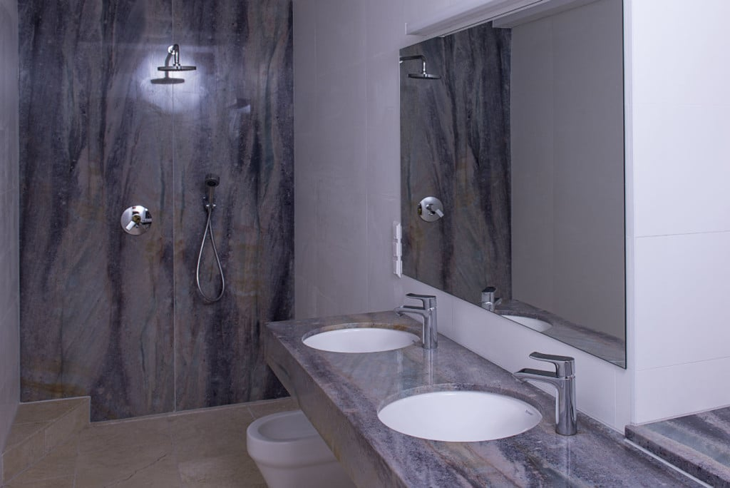 Luxusbad mit Waschbecken und Duschwand aus Quarzit poliert in braun und grau