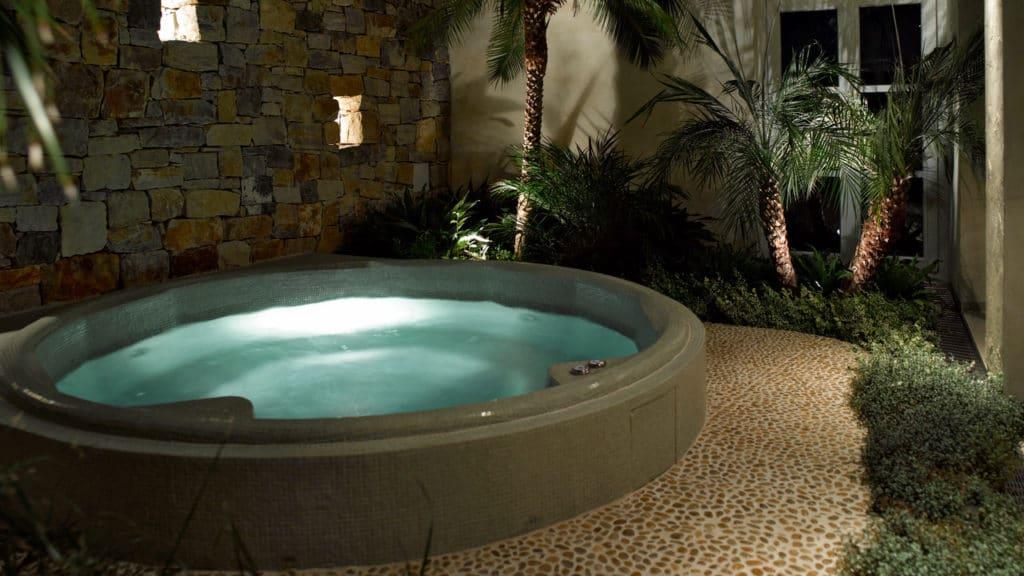 Whirlpool außen und innen mit Glasmosaik überzogen, am Boden Flachkieselsteine, Bruchsteinmauer