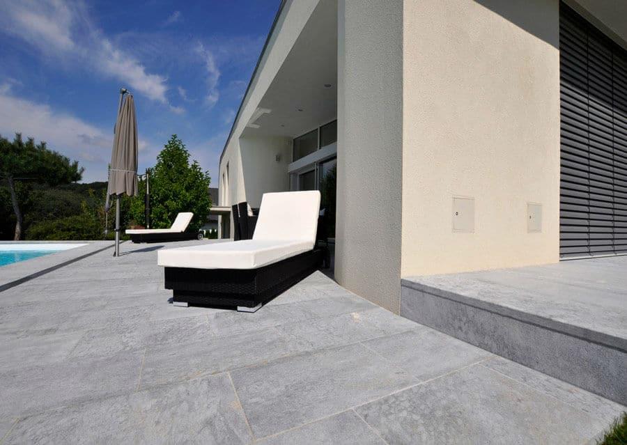 Kalksteinterrasse in grau mit Pool und Liegen vor modernem Haus