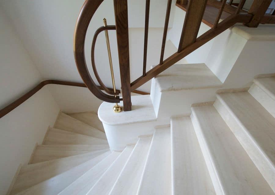 Natursteintreppe in weiß mit dunkelbraunem Holzgeländer